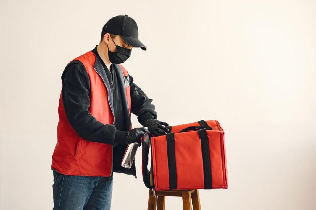 Motoboy de casaco laranja, calça jeans e boné preto organiza uma mochila de transporte delivery em cima de um banco.