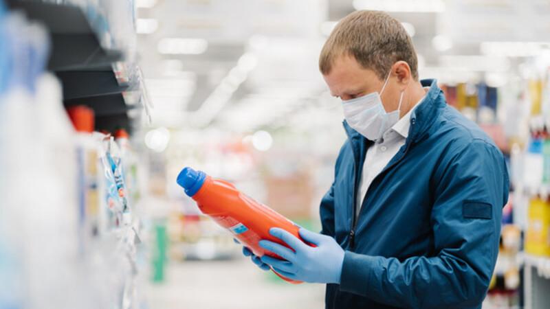 Homem usando máscara em um supermercado. Ele segura uma embalagem de um produto de limpeza.