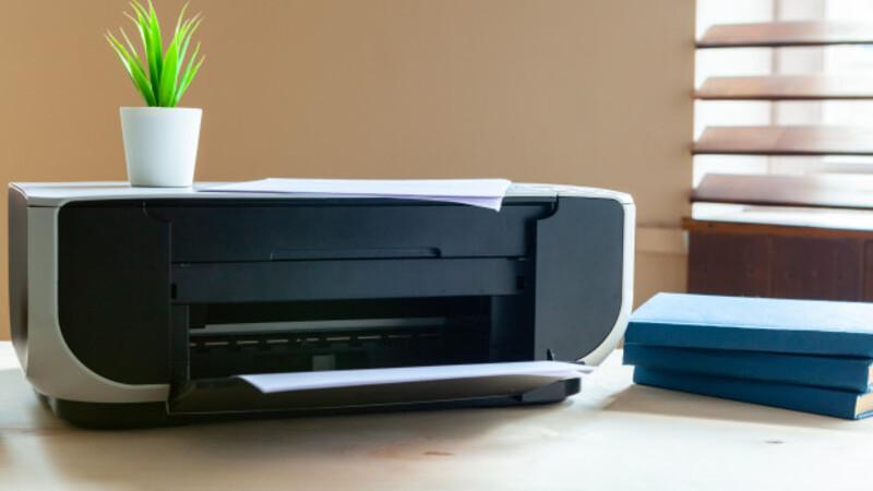 Impressora preta sob uma mesa. Ao lado, livros azuis e uma plantinha verde em cima dela. Ao fundo, uma janela aberta.
