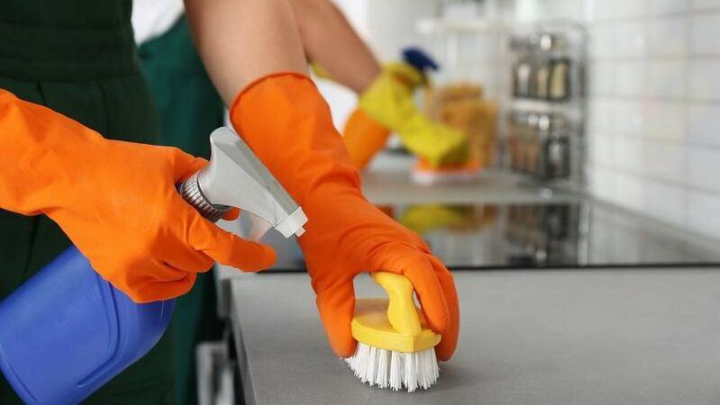 Mãos de pessoa usando luvas de borracha alaranjadas e segurando escova e produto de limpeza sobre balcão.