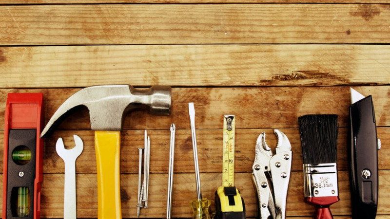 Chave de fenda, martelos, pregos, chave Phillips, trena, chave inglesa, pincel e estilete sobre superfície de madeira.