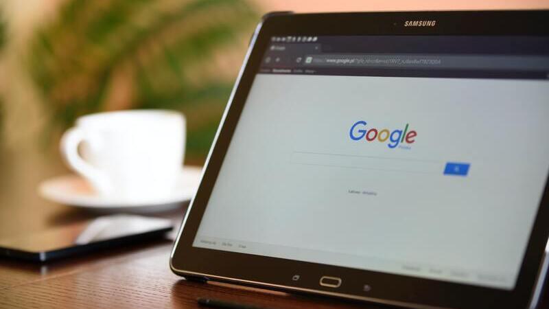 Tablet sob uma mesa de madeira marrom com a tela do Google. Em segundo plano, uma xícara branca e um celular.