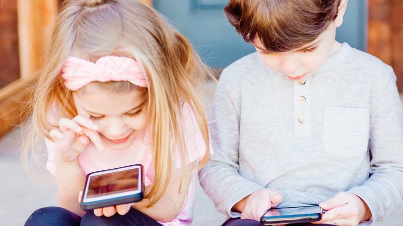 Menina loira com faixa rosa no cabelo sentada segurando smartphone. Ao lado, um menino de camisa cinza segurando smartphone.