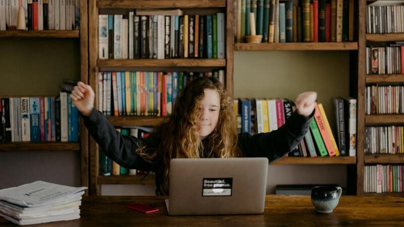 Menina com os braços levantados para cima em posição de vitória na frente de um notebook. Ao fundo, uma estante com livros.