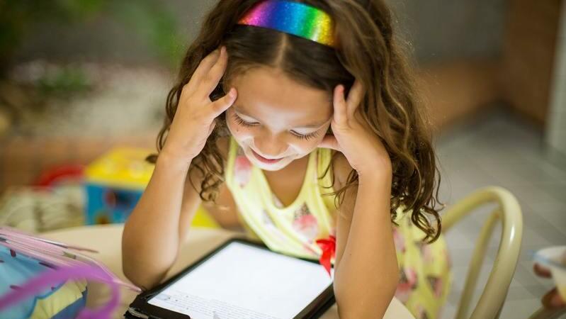 Menina olhando tablet com as mãos na cabeça. Ela está sentada em uma mesa e usa uma tiara colorida.