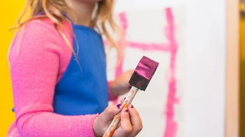 Menina segurando pincel com tinta cor de rosa perto de tela pintada de rosa.