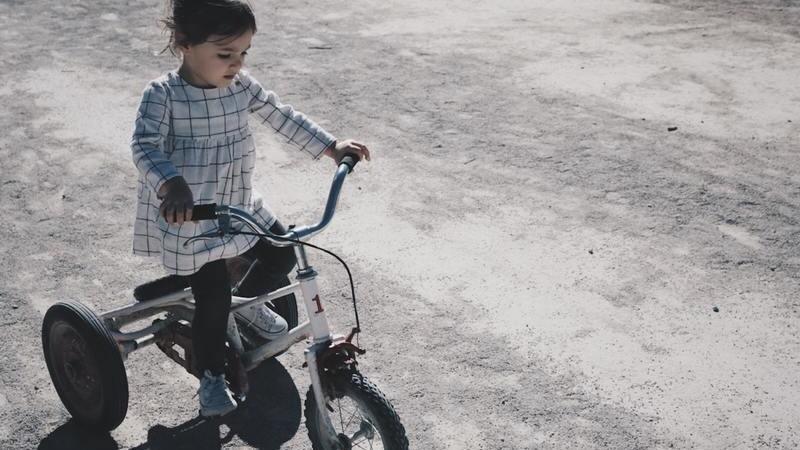 Em chão de terra, uma menina anda com um triciclo. Ela veste uma blusa de listras.