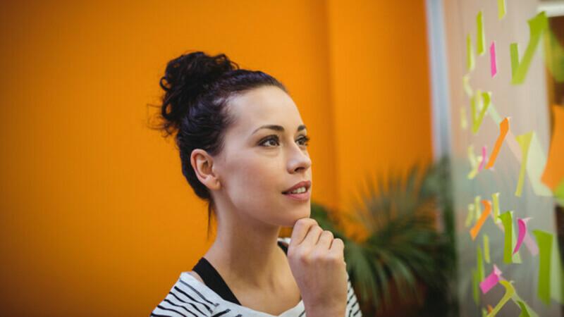 Em fundo laranja, mulher está com a mão no queixo olhando para um quadro cheio de post-its.