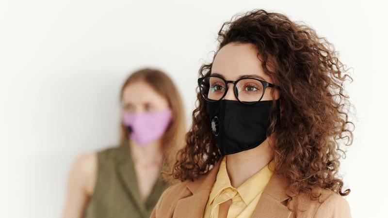 Duas mulheres com roupas sociais usando máscaras de proteção.