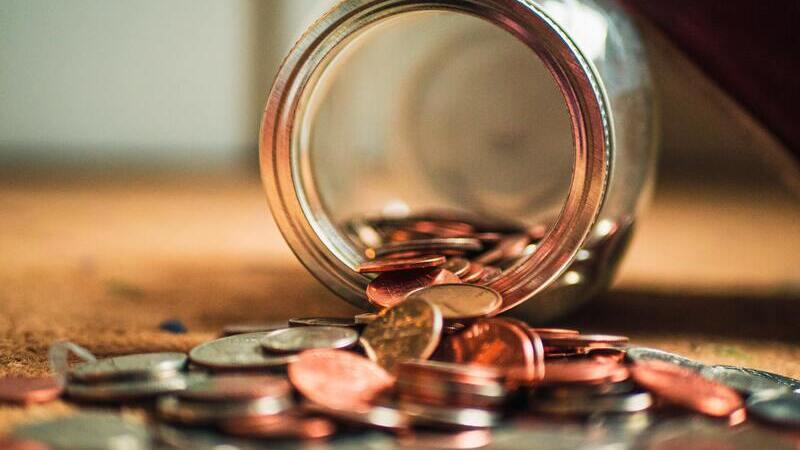 Em um chão de carpete, um pote de vidro está tombado com várias moedas saindo dele.