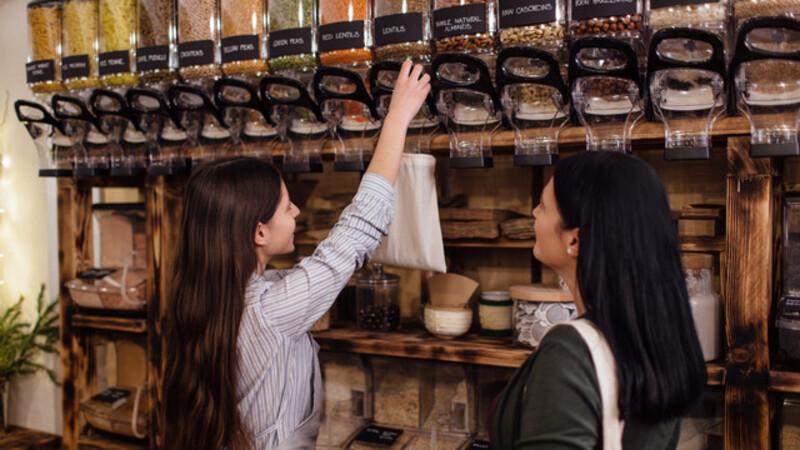 vendedora retirando produtos a granel e colocando em embalagem ecológica para a sua cliente que fica satisfeita observando.