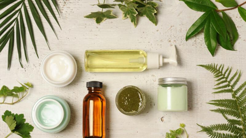 Vários produtos alimentícios e cosméticos sustentáveis: frutas, verduras, grãos, óleos sob um fundo branco.