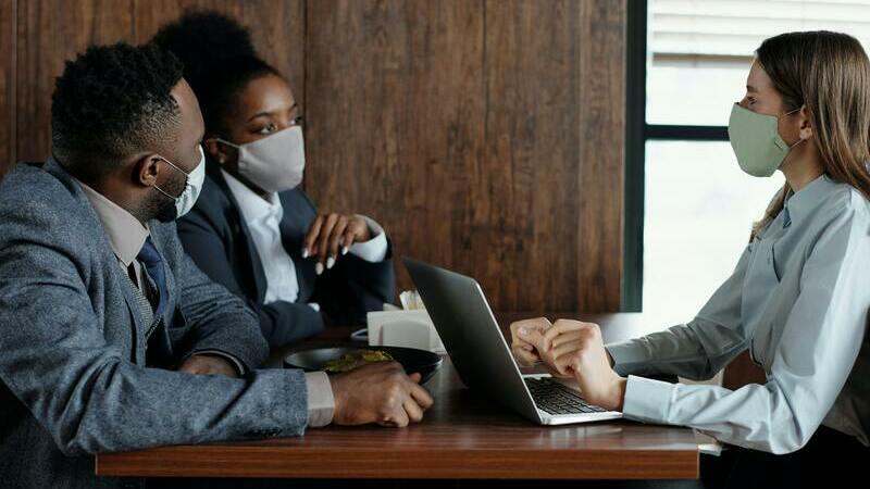 Um homem e uma mulher conversando com outra mulher, todos usam máscaras de proteção. Há um computador portátil sobre a mesa.