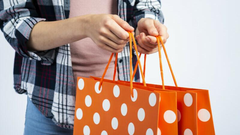 Mãos de uma mulher segurando duas sacolas laranjas de compras.