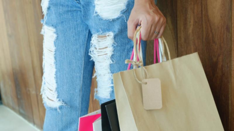 Uma pessoa usando calça jeans azul com rasgos e segurando sacolas de compras na mão.