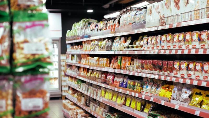 Foto apresentando um supermercado local, com gôndolas cheias de produtos e refrigerador ao fundo