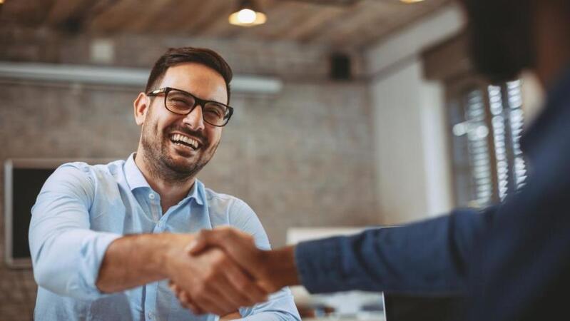 Homem de barba e óculos sorrindo com o braço estendido para um aperto de mão com outra pessoa.