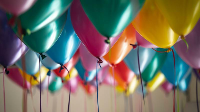 Vários balões coloridos amarrados com fita e pendurados no teto