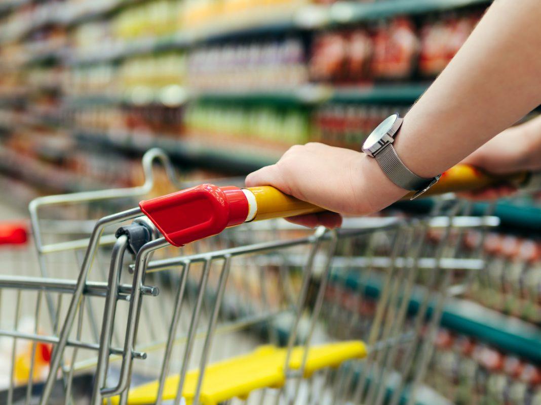 braços de pessoa apoiados em carrinho de supermercado com prateleira de produtos no fundo desfocado