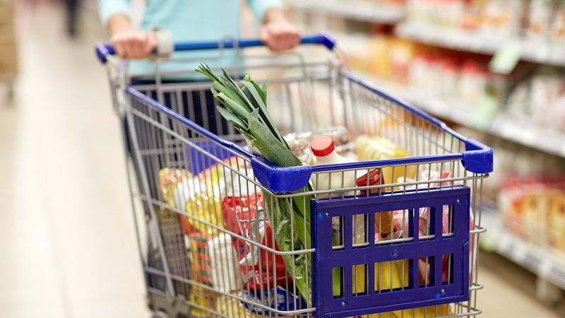 carrinho de supermercado cheio de produtos empurrado por uma pessoa andando em corredor de supermercado que aparece embaçado ao fundo