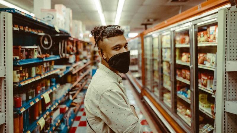 homem de máscara parado de perfil no meio de corredor de varejo de vizinhança com refrigeradores na sua frente e gôndola com produtos atrás