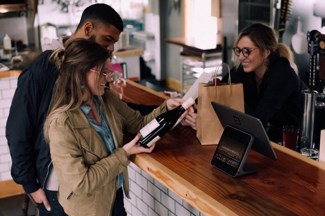 mulher sorrindo e segurando garrafa de vinho, homem parado com as mãos no bolso próximo de balcão de loja, operadora de caixa sorrido do outro lado do balcão próxima de sacola de compras de papel e tablet