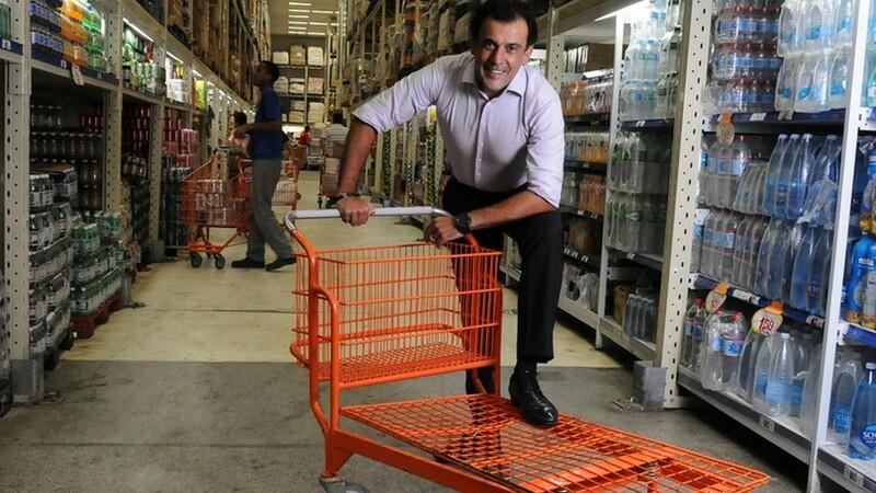homem com o pé apoiado em carrinho de compras laranja parado em corredor de atacarejo