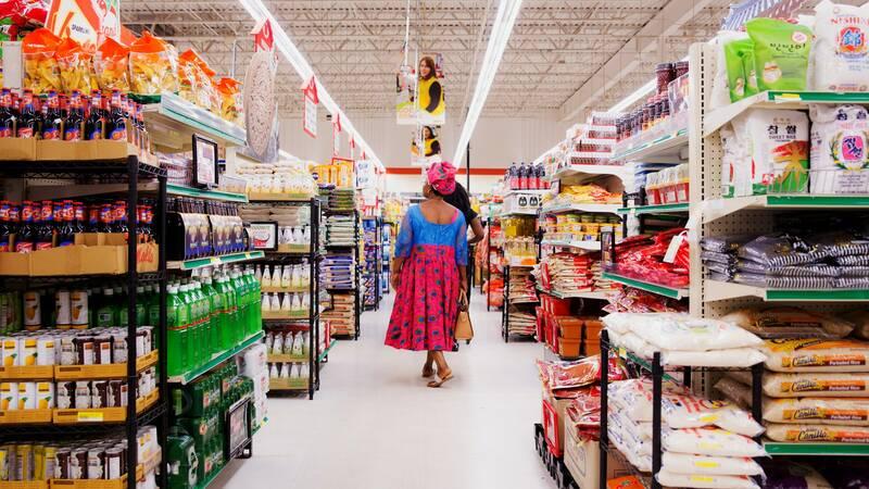 mulher de costas andando em corredor de supermercado com prateleiras de produtos à esquerda e à direita