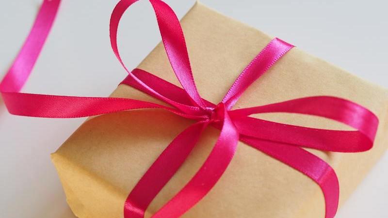 Pacote de presente com laço de fita cor de rosa e embrulho de papel craft.