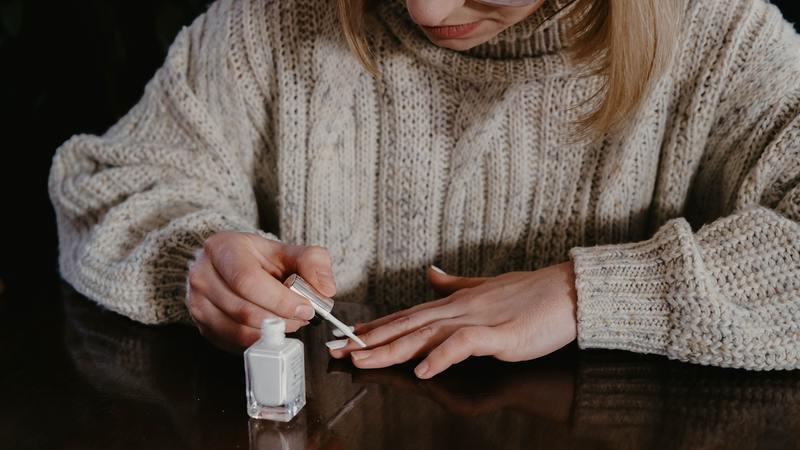 mulher usando tricô bege com as mãos apoiadas sobre superfície de madeira segurando aplicador de esmalte branco sobre as unhas ao lado de vidro de esmalte branco aberto