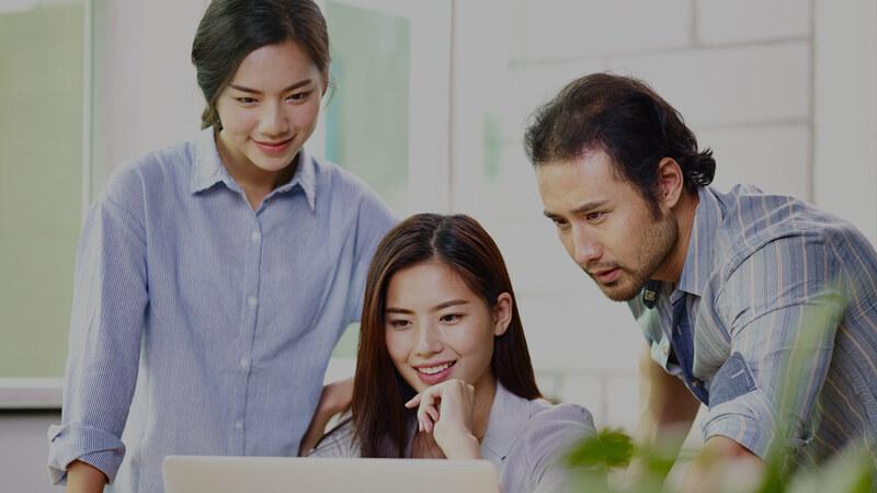 mulher asiática com a mão no queixo olhando para tela de notebook entre mulher asiática de pé com as mãos na cintura e homem asiário com o corpo curvado olhando na mesma direção
