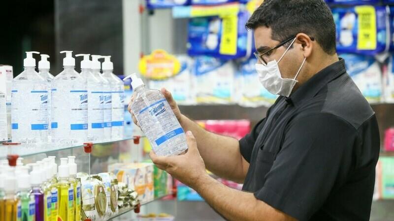 Homem parado em frente a prateleira de produtos de farmácia segurando embalagem grande de álcool gel.