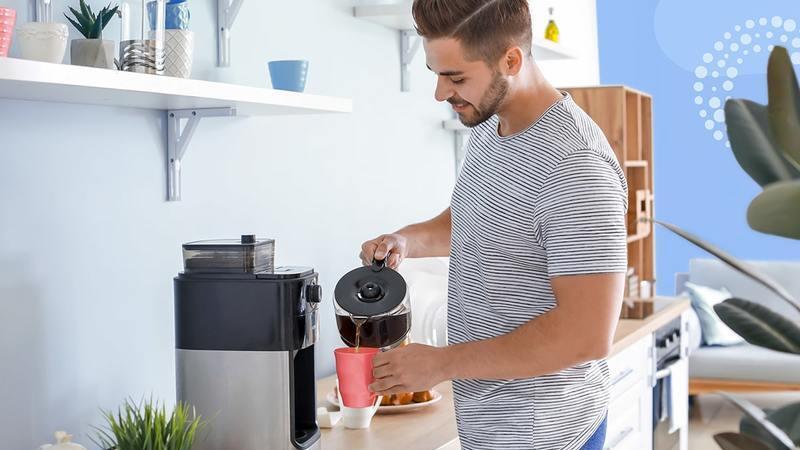 homem se servindo de café com jarra de cafeteira e copo colorido em cozinha de escritório