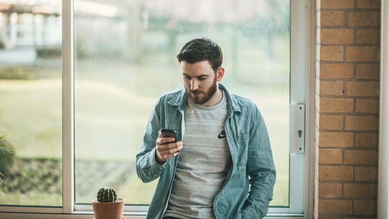 homem parado na frente de uma janela com vista para área externa segurando smartphone e olhando para o aparelho