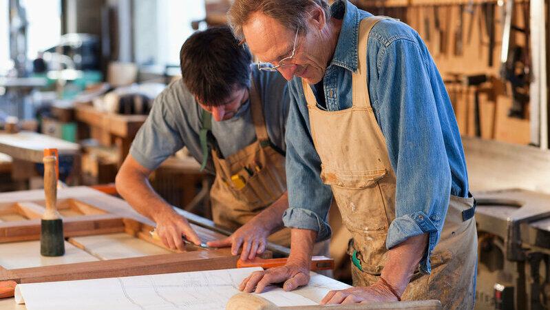 homem idoso usando avental de trabalho sobre camisa jeans com os braços apoiados sobre folha com projeto de marcenaria ao lado de homem jovem usando avental de trabalho usando régua para medir objeto de madeira em oficina