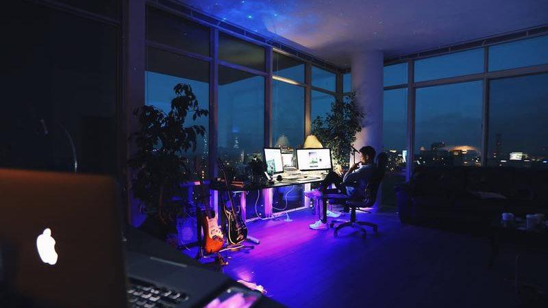 homem sentado sozinho em escritório durante a noite com iluminação apenas da tela dos computadores