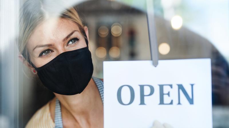 mulher de máscara e luvas segurando placa escrito OPEN na porta de loja