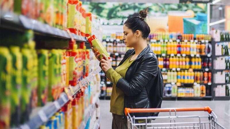 mulher segurando produto em frente a gondola de supermercado