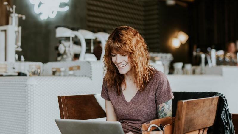Mulher ruiva sentada em café segurando notebook no colo. Ao fundo, um restaurante.