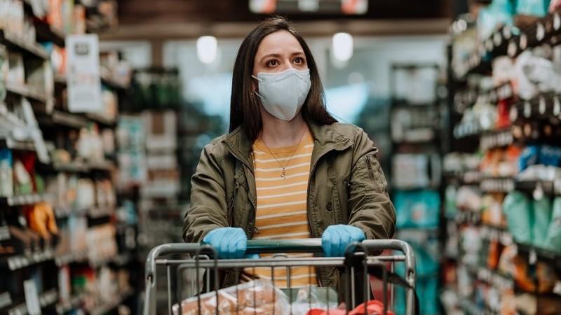 Mulher usando máscara e luvas parada entre duas prateleiras de produtos empurrando carrinhos de compras.