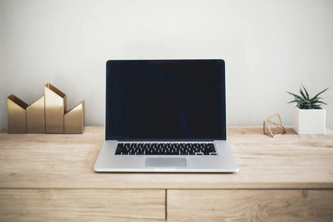 notebook aberto sobre mesa de madeira