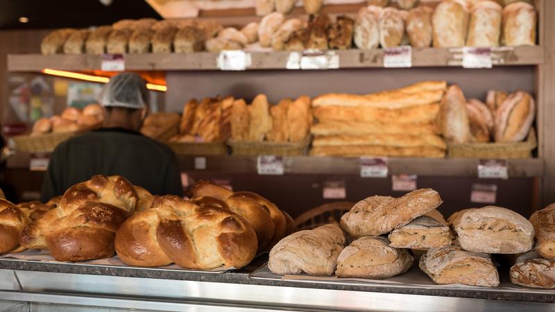 mostruário de padaria com pães diversos sobre o balcão e pessoa de costas usando touca ao fundo
