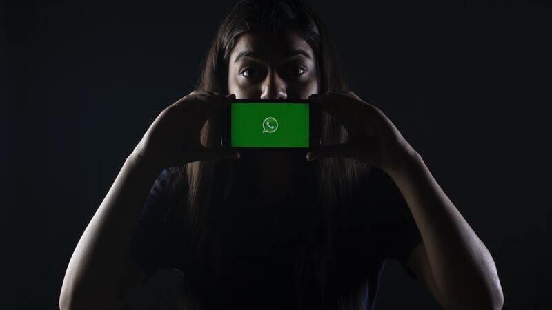 pessoa segurando smartphone em frente a boca com logo do Whatsapp na tela