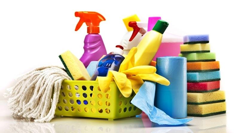 cesta com luva de borracha, produtos de limpeza, esponja e esfregão ao lado de rolo de sacos de lixo azuis e esponjas empilhadas