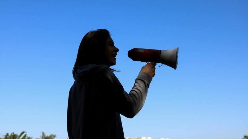 silhueta de pessoa de perfil segurando megafone próximo ao rosto contra a luz do céu azul