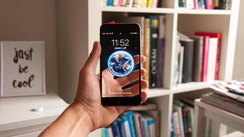 mão humana segurando smartphone em frente a estante de livros