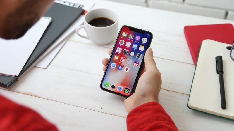 mão segurando smartphone perto de mesa com caderno, caneta e xícara de café