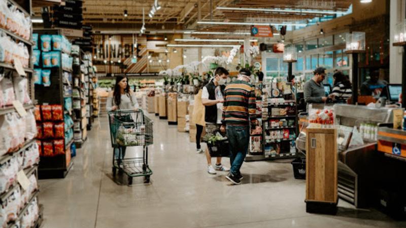 Região do caixa de supermercado com mulher empurrando carrinho. À sua frente há dois homens segurando cesta de compras.