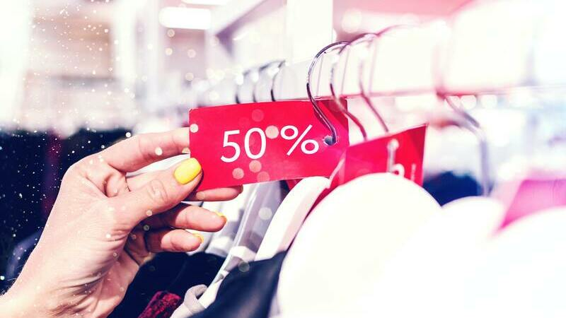 Uma mão segurando cupom vermelho de 50% afixado em cabide de roupas