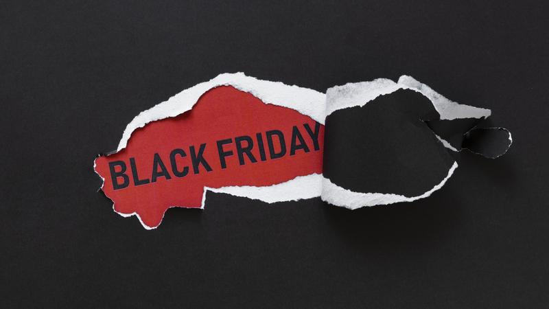 """Superfície de papel preto com rasgo no centro. Por trás do rasgado, uma superfície vermelha com """"Black Friday"""" escrito."""